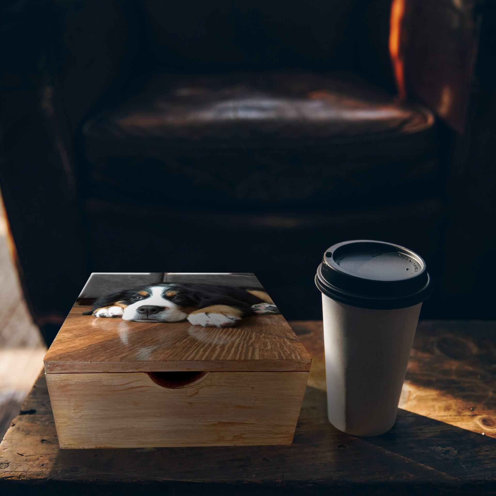 Caja de madera de color amarillo para guardar sobres de Té, en la tapa se encuentra la foto de un perro de color negro y blanco. Este objeto se apoya sobre una mesa de madera de color cafe. Por otro lado, se evidencia a su lado un vaso de cafe.