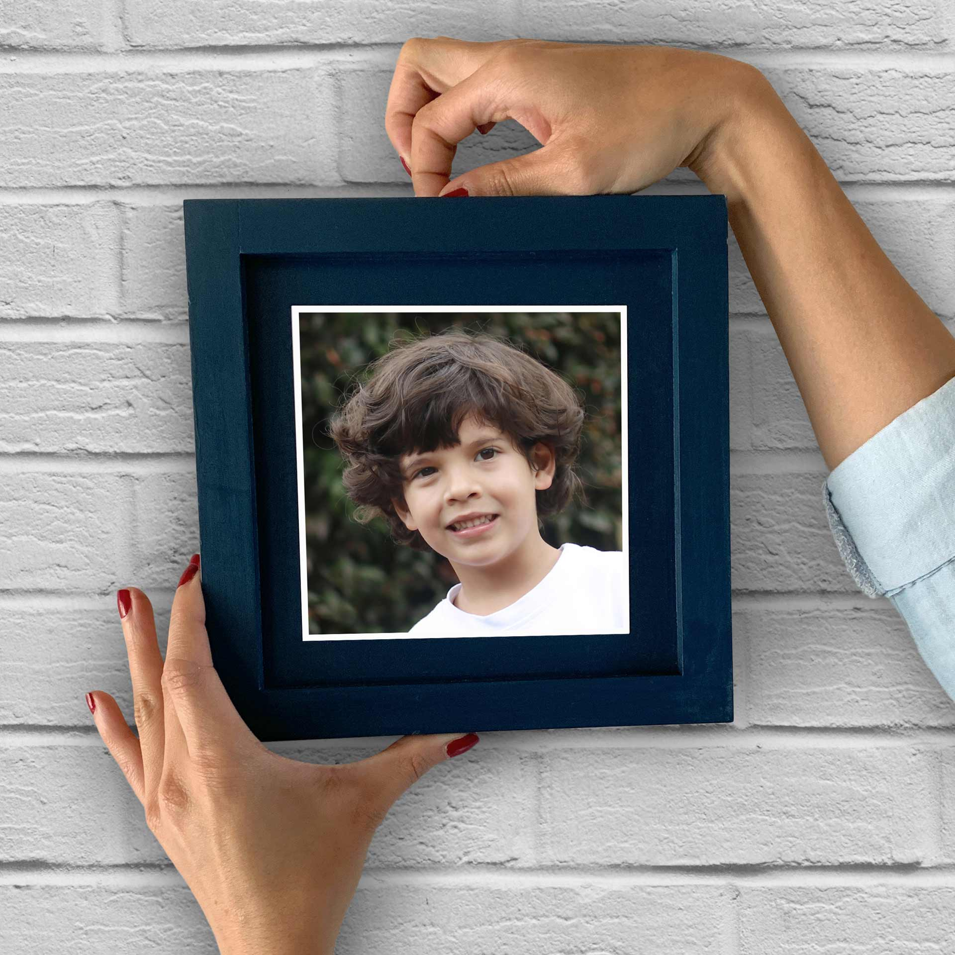 cuadro de color azul que posee la foto de un niño, este cuadro se apoya sobre una pared de ladrillo de color blanco.